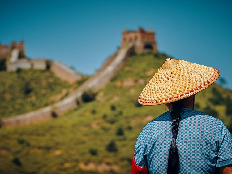 Chinese person wearing traditional hat at Great Wall