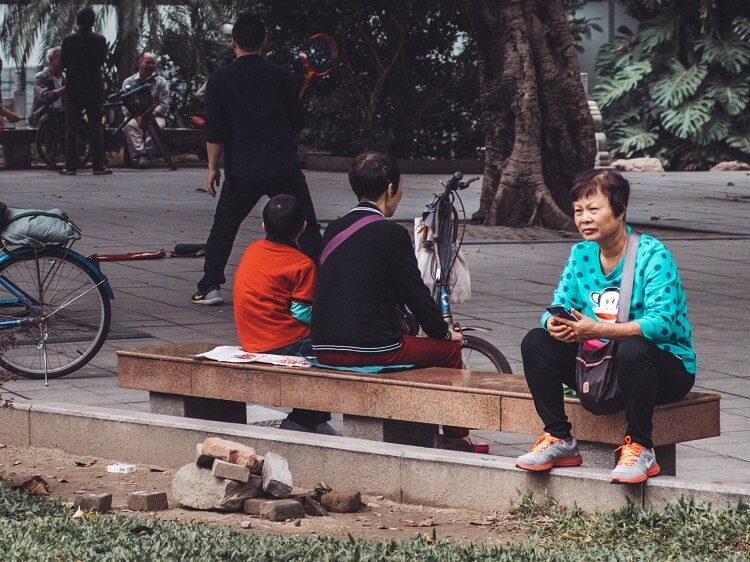 Chinese woman sitting on park bench