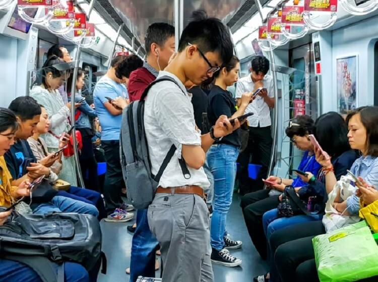 Chinese guy looking at phone on subway train