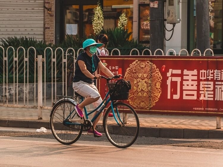 Woman wearing pollution mask while riding bicycle