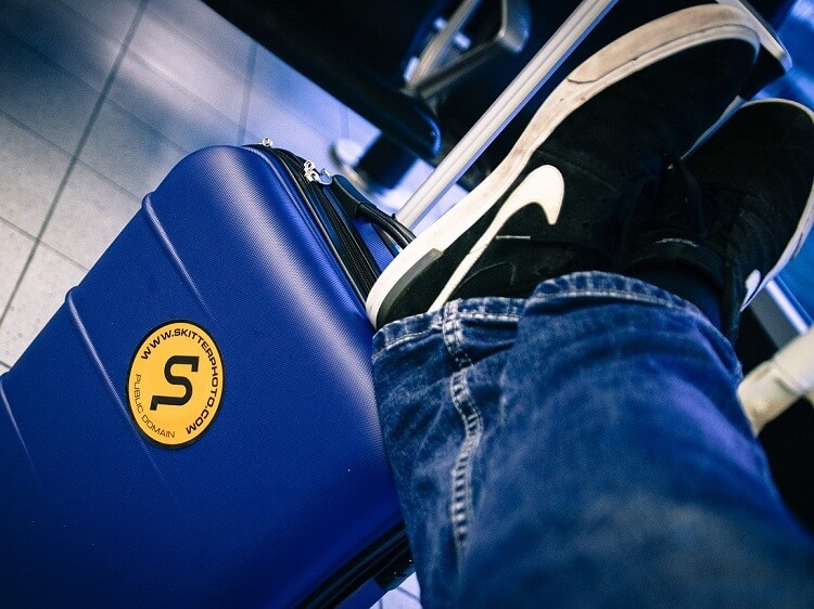 Person wearing jeans with feet on suitcase