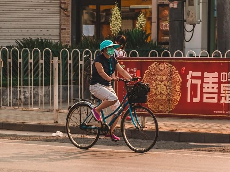 Chinese woman on bike wearing face mask