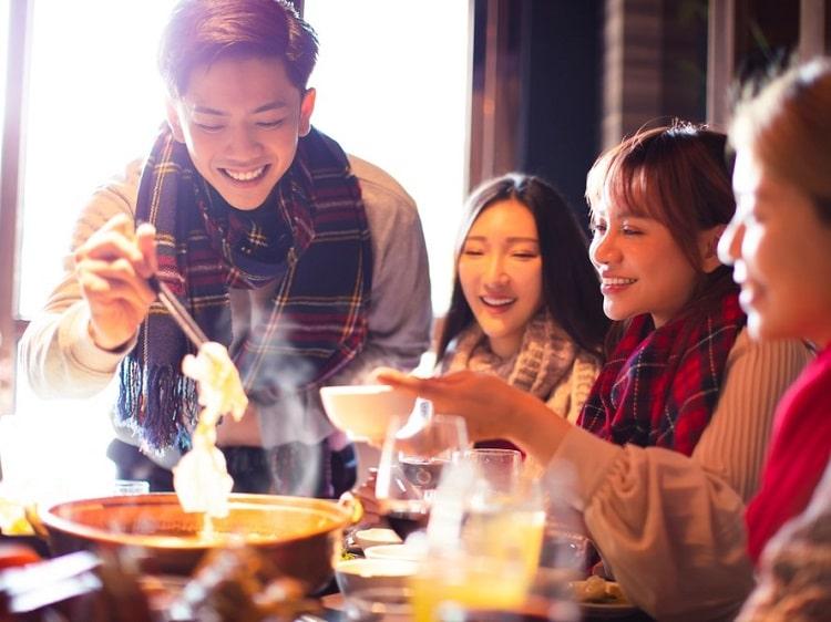 Chinese girls and guy eating hotpot
