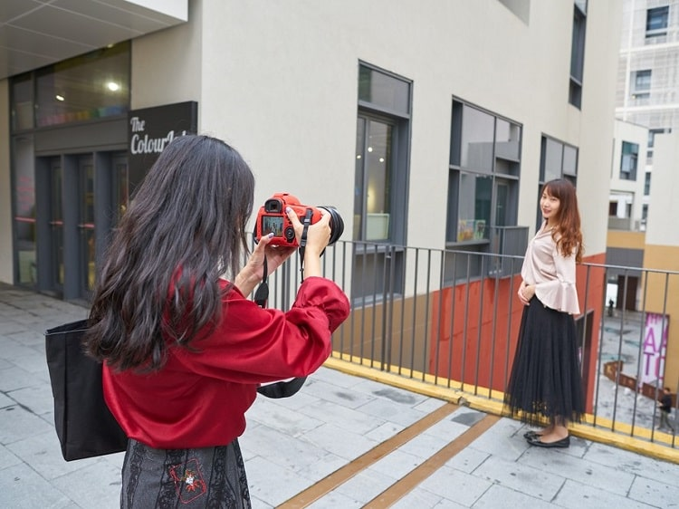 Chinese woman taking photo of another woman