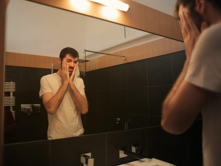 Sad guy holding his face in mirror