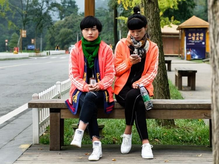 Chinese girls sitting on park bench
