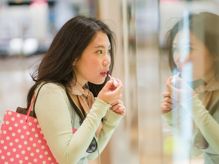 Chinese girl putting on makeup in reflection