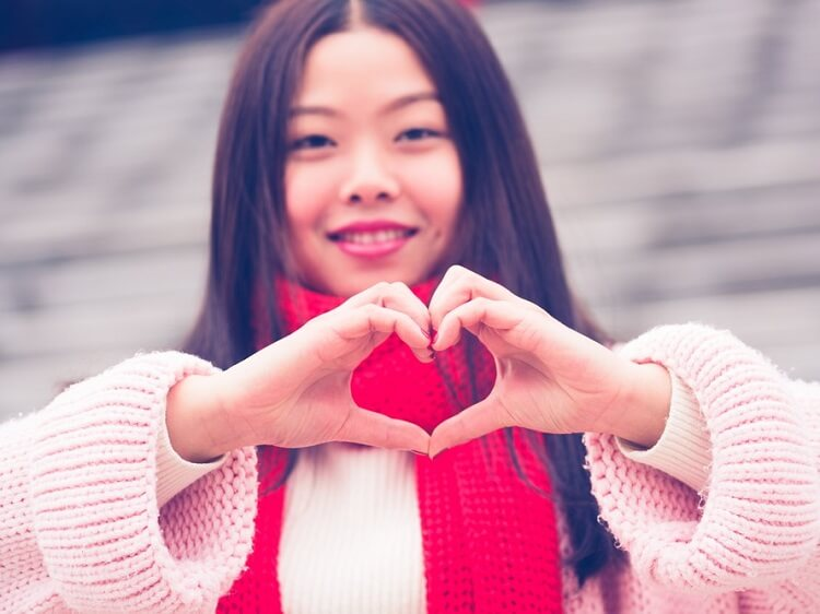 Chinese girl making a heart symbol