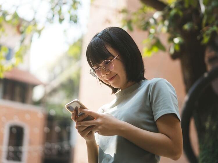 Smiling Chinese girl holding phone