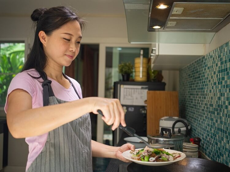 Chinese woman cooking in kitchen over wok
