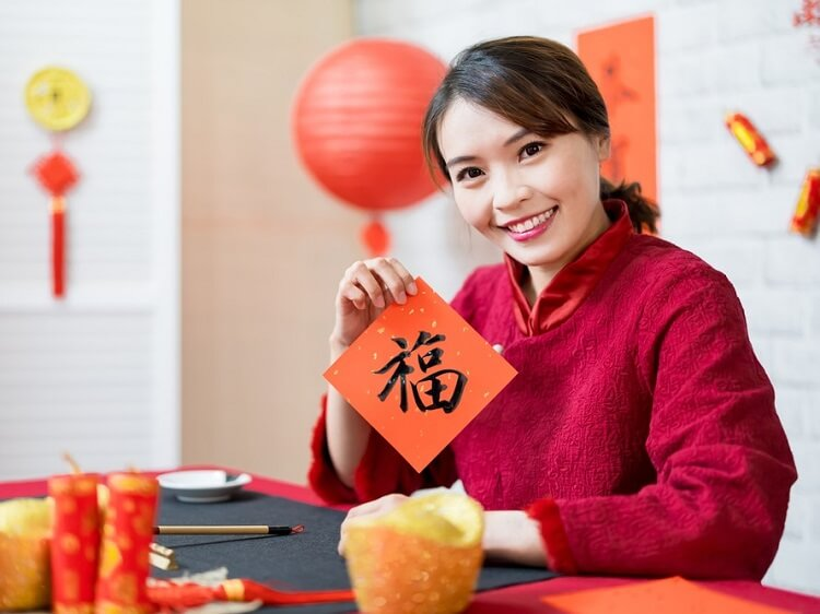 Chinese woman holding lucky fortune sign