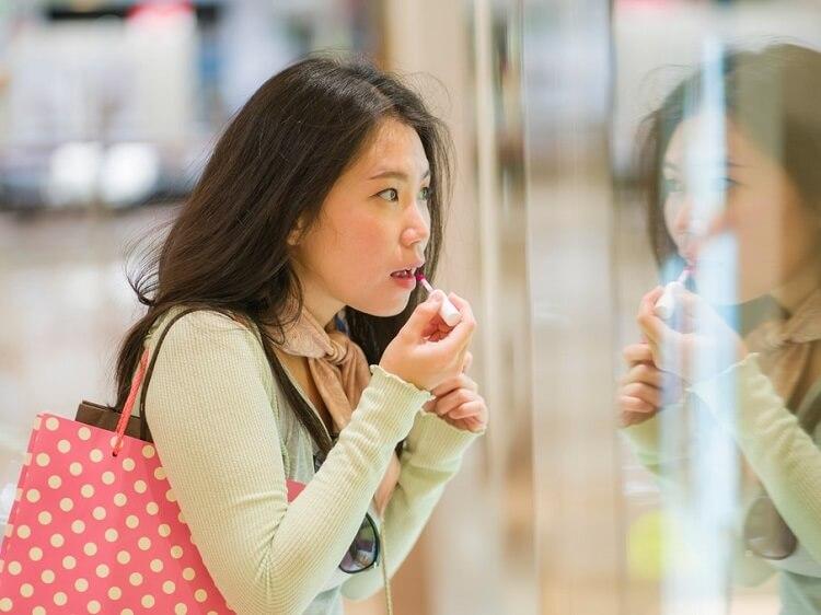 Chinese woman applying lipstick