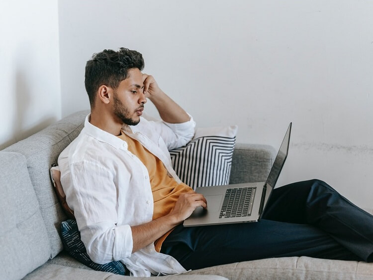 Man on couch looking for jobs online
