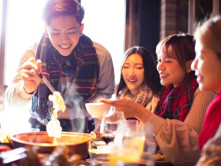 Smiling young Chinese people eating
